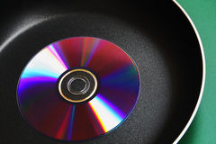 Compact disk on frying pan Stock Photos
