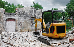 Compact Excavator on Small Building Site. A compact excavator on a small domestic building site where a breezeblock building has just been demolished. The Stock Photo