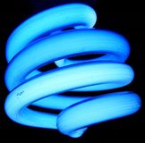 Compact Flourescent Lightbulb. A blue compact flourescent lightbulb representing power and energy efficiency. Dust on the curly bulb suggests extended life Royalty Free Stock Photo