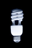 Compact fluorescent bulb. Energy efficient and environmentally friendly - on black background Royalty Free Stock Photos