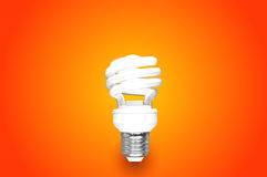 Compact Fluorescent Bulb on orange background (CFL). Compact Fluorescent Bulb on orange background CFL Royalty Free Stock Image