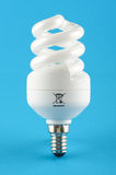 Compact fluorescent energy saving light bulb isolated on the blue background Stock Photos