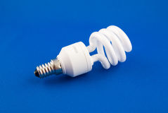 Compact fluorescent lamp. On a blue surface Stock Photos
