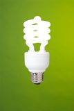 Compact fluorescent light bulb. A compact fluorescent light bulb against a green background Royalty Free Stock Photography