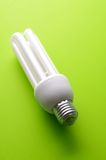 Compact Fluorescent Light Bulb. On green yellow background stock photography
