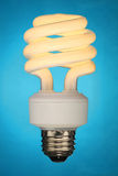 Compact Fluorescent Light Bulb. (CFL) on blue background Stock Photos