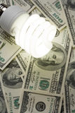 Compact Fluorescent Light bulb and dollar Stock Photography