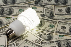 Compact Fluorescent Lightbulb and dollar Stock Photography