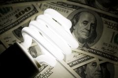 Compact Fluorescent Lightbulb and dollar royalty free stock photography