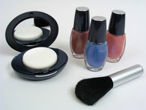 Compact & Nail Polish. A compact with nail enamels & cosmetic brush on an off-white background. (background is grayish-white, not pure white Stock Images