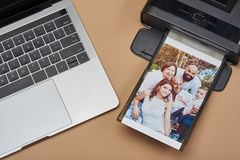 Compact printer with family image. And laptop above top view stock photo