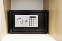 Compact safe on shelf of cabinet Stock Image