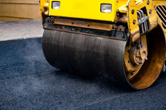 Compact steamroller flatten out the asphalt Royalty Free Stock Images