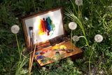 Compact vintage painter's case on grass Royalty Free Stock Photos