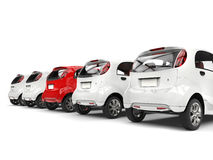 Compact white electric cars in a row - red stands out - back view Royalty Free Stock Photos