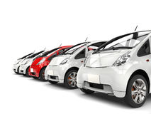 Compact white electric cars in a row - red stands out Royalty Free Stock Images