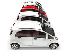 Compact white electric cars in a row - red stands out Stock Photos