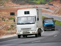 Compact white truck and old beat up blue truck Royalty Free Stock Photo