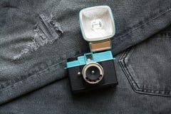 Compacte uitstekende plastic filmcamera op donkere grijze jeans stock afbeelding