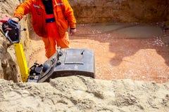 Compacteur de compactage de plat de vibration de base de travailleur photographie stock libre de droits