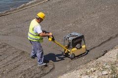 Compacteur de plat de vibration sur un chantier de construction de rivière Images libres de droits
