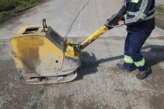 Compacteur vibratoire de plat d'utilisation de travailleur au site de construction de routes Photographie stock