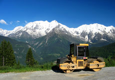 Compactor ahead Mont Blanc. A roadworks compactor ahead Mont Blanc in Haute Savoie, France Royalty Free Stock Photo