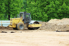Compactor is compacting the surface of the earth. Construction of the city stadium. Compactor is compacting the surface of the earth. Construction of the city Royalty Free Stock Images