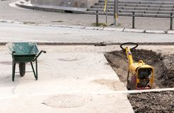 Compactor machinery and construction trolley on the street reconstruction site. Royalty Free Stock Photos