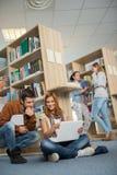 Compañeros de clase que estudian junto en el ordenador portátil en biblioteca Foto de archivo libre de regalías