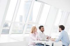 Compañeros de trabajo jovenes que tienen sesión de la reunión de reflexión en oficina moderna Imágenes de archivo libres de regalías