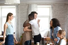 Compagni che abbracciano accogliendosi alla riunione in caffè immagini stock