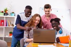Compagni del gruppo che guardano insieme lezione online sul computer portatile immagine stock libera da diritti