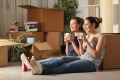 Compagni di camera felici che muovono caffè bevente di riposo domestico fotografia stock libera da diritti