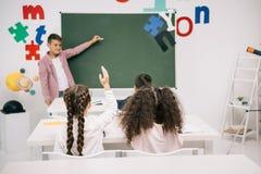 Compagni di classe che esaminano scolaro che risponde vicino alla lavagna in bianco Fotografie Stock Libere da Diritti