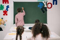 Compagni di classe che esaminano scolaro che risponde vicino alla lavagna in bianco Immagine Stock