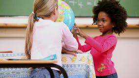 Compagni di classe che esaminano un globo Immagini Stock