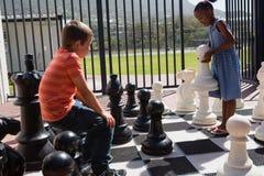 Compagni di classe che giocano insieme ai grandi scacchi Immagine Stock