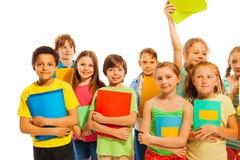 Compagni di classe che stanno insieme ai manuali Fotografie Stock Libere da Diritti
