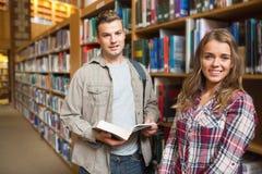 Compagni di classe felici che stanno nella biblioteca che sorride alla macchina fotografica Fotografia Stock Libera da Diritti
