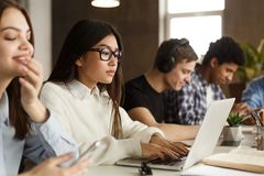 Compagni di classe internazionali concentrati che preparano per gli esami in biblioteca immagine stock