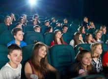 Compagni di scuola che guardano fumetto nel corridoio del cinema Fotografie Stock Libere da Diritti