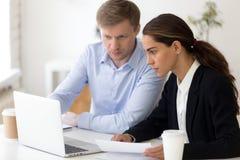Compagni di squadra che lavorano insieme facendo uso del computer che si siede nel luogo di lavoro fotografia stock libera da diritti