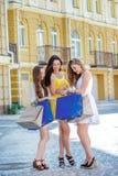 compagnie Filles tenant les paniers et la promenade sur les boutiques Photo libre de droits