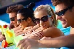 Compagnie heureuse dans l'eau avec le cocktail Photo stock