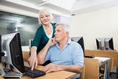 Compagno di classe maschio d'aiuto della donna nel laboratorio del computer Immagine Stock Libera da Diritti