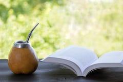 Compagnon de Yerba dans le matero de courge avec le livre ouvert sur la table en bois photo stock