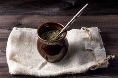 Compagnon de Yerba dans le matero en céramique avec le bombilla sur le sac de toile sur la table en bois Photo libre de droits