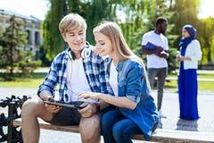 Compagnons décontractés d'université causant dehors et souriant photo libre de droits