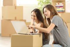 Compagnons de chambre heureux recherchant sur la ligne et la maison mobile Photos stock